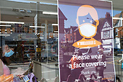 With most shops now open but with retail sales suffering due to the Coronavirus pandemic, shoppers wearing face maks at Sainsburys supermarket, which became compulsory in shops on the 24th July, out shopping on Kings Heath High Street on 31st July 2020 in Birmingham, United Kingdom. Coronavirus or Covid-19 is a respiratory illness that has not previously been seen in humans. While much or Europe has been placed into lockdown, the UK government has put in place more stringent rules as part of their long term strategy, and in particular social distancing.