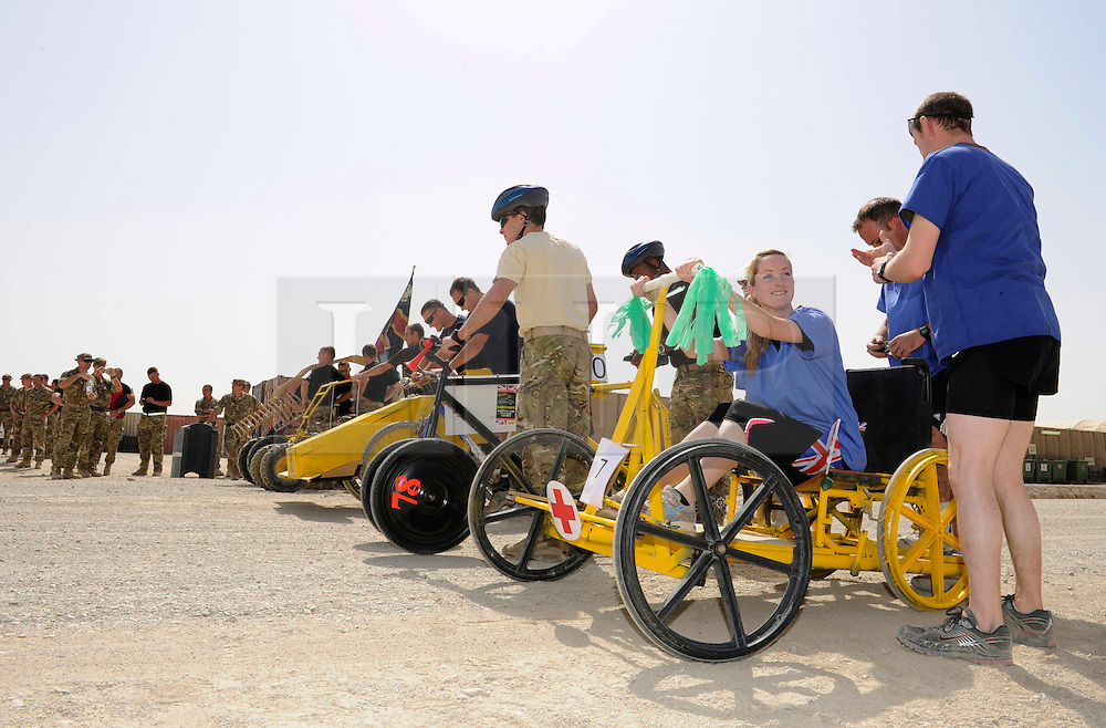 © Licensed to London News Pictures. 18/08/2011. Bastion, Afghanistan. British soldiers line up at the start of a 'make your own' Kart race at Camp Bastion.  The race was organised to raise money for Kart Force, a UK based charity that modifies go karts so that they can be used by amputees and injured soldiers.  Photo credit : Sergeant Alison Baskerville/LNP