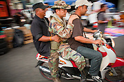 """May 12 - BANGKOK, THAILAND: Maj. Gen. KHATTIYA """"Seh Daeng"""" SAWASDIPOL (center, in army fatigues) is driven through the Red Shirt camp in Bangkok on the back of a motor scooter Wednesday. Seh Daeng, as he is known, has emerged as the Red Shirts unofficial military commander. He has organized the barricades that ring the Red Shirt camp and has threatened to organize a guerilla campaign against the government if the Red Shirt protest is crushed by force. Seh Daeng is a hero to many Thais because he is credited with crushing Thailand's communist insurgency in the 1970's and 80's. He was the commander of Thailand's Internal Security Operations Command but after his political activities became apparent he was made the head aerobics instructor for the Thai army. He is now seen as one of the major personalities destabilizing the country and the government alleges that he is behind many of the grenade attacks and drive by shootings directed at government buildings and officials and he is wanted for a long list of felony offenses including weapons charges and terrorism related charges. Although some Red Shirts have officially repudiated him, he is still frequently seen around the Reds' barricades. The army has started proceedings to fire him, but he remains a general on active duty.   PHOTO BY JACK KURTZ"""