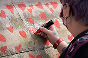 Red hearts that form the National Covid Memorial Wall, a tribute to the 150,000-plus British victims of the Coronavirus pandemic on 1st April 2021, in London, United Kingdom. Bereaved family and friends of Covid-19 victims have started working on the wall located outside St Thomas' Hospital. (Richard Baker / In Pictures via Getty Images)
