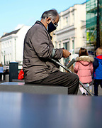 A man sits on a bench to read a shopping list in High Street, Cheltenham during the ongoing Coronavirus pandemic.