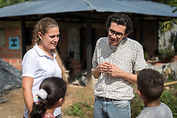 16 November 2018, San José de León, Mutatá, Antioquia, Colombia: Rev. John Hernández, a Lutheran pastor from Medellín (right) accompanies communities in the Antioquia area in northwest Colombia. Here, in conversation with children in the community of San José de León, together with project volunteer Octa Capella (left). Following the 2016 peace treaty between FARC and the Colombian government, a group of ex-combatant families have purchased and now cultivate 36 hectares of land in the territory of San José de León, municipality of Mutatá in Antioquia, Colombia. A group of 27 families first purchased the lot of land in San José de León, moving in from nearby Córdoba to settle alongside the 50-or-so families of farmers already living in the area. Today, 50 ex-combatant families live in the emerging community, which hosts a small restaurant, various committees for community organization and development, and which cultivates the land through agriculture, poultry and fish farming. Though the community has come a long way, many challenges remain on the way towards peace and reconciliation. The two-year-old community, which does not yet have a name of its own, is located in the territory of San José de León in Urabá, northwest Colombia, a strategically important corridor for trade into Central America, with resulting drug trafficking and arms trade still keeping armed groups active in the area. Many ex-combatants face trauma and insecurity, and a lack of fulfilment by the Colombian government in transition of land ownership to FARC members makes the situation delicate. Through the project De la Guerra a la Paz ('From War to Peace'), the Evangelical Lutheran Church of Colombia accompanies three communities in the Antioquia region, offering support both to ex-combatants and to the communities they now live alongside, as they reintegrate into society. Supporting a total of more than 300 families, the project seeks to alleviate the risk of re-victimization,