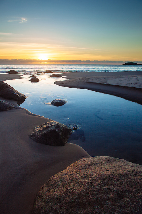 The outlet of Warrawilla Lagoon flowing around boulders and sand to the ocean. Hinchinbrook Island.