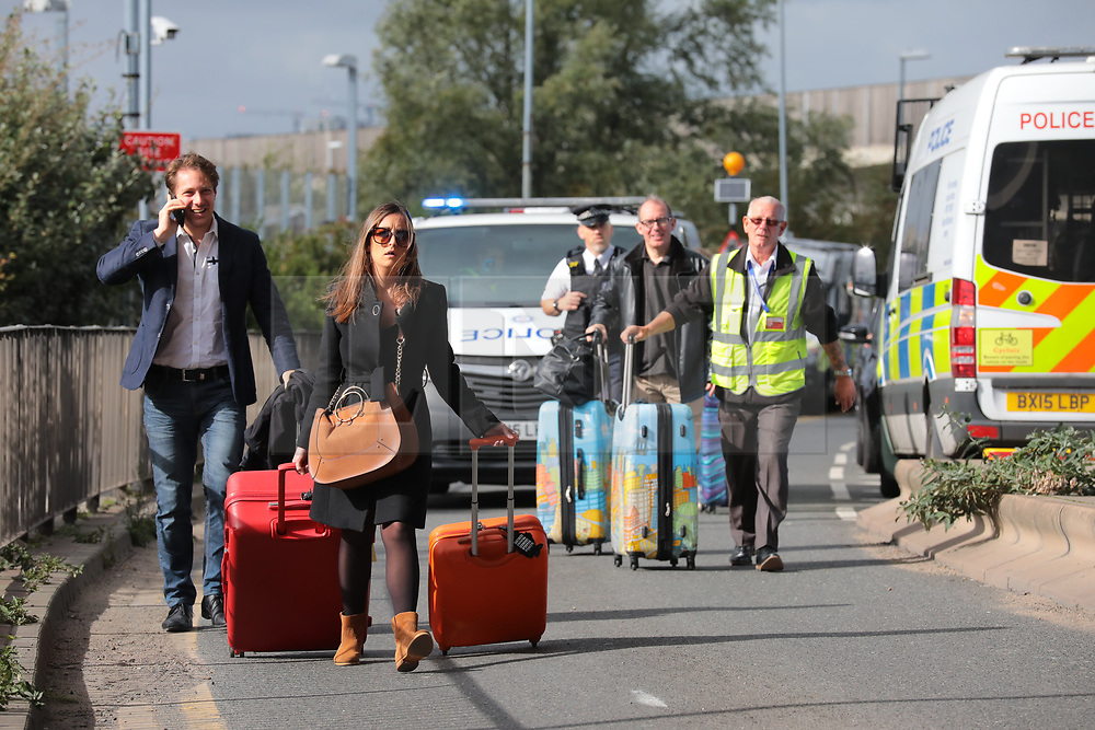 © Licensed to London News Pictures. 10/10/2019. London, UK. Passengers wheel their suitcases up the road as Extinction Rebellion protesters block road access to London City Airport. Protesters plan to occupy the terminal building in a 'Hong Kong-style' shutdown as part of ongoing protests calling on government departments to tackle the Climate Emergency. Photo credit: Rob Pinney/LNP