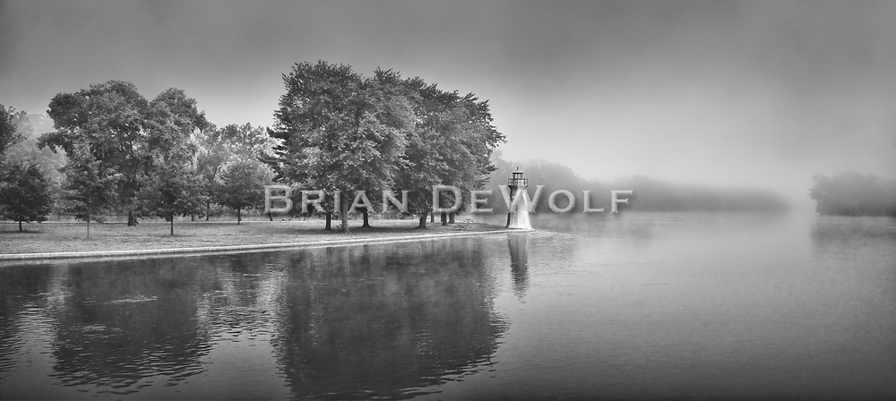 """This is an open edition print. Canvas prints have a 2 inch black border so it can be gallery wrapped. The print is made using pigmented inks on museum-grade canvas or watercolor paper. Each print also gets a light coating of lacquer protective spray. Each print is hand signed by Brian DeWolf.  When Colonel Fabyan wanted to build a bridge across the Fox River joining his properties on both sides, the state of Illinois insisted that it must meet criteria for spanning a navigable waterway. The colonel didn't see any sense in that since a series of dams obstructed the river every few miles and in the dry months it was about waist deep in the channel. About the only things that """"navigated"""" the Fox were canoes and wading fishermen.<br /> People wonder why there is a lighthouse on the Fox River. Colonel Fabyan built it as a sarcastic edifice to the State's opinion. Today it still pretends to warn ships that have never navigated the Fox, nor ever will."""