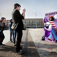 Nederland, Amsterdam , 14 maart 2014.<br /> Jelle van Piratenpartij west fotografeert passantan op het Mercatorplein achter zijn Wally bord.<br /> Op vrijdag 14 maart voert de Piratenpartij Amsterdam West op het Mercatorplein actie tegen het afbreken van onze privacy. Met een groot 'Wally'-bord, het titelkarakter uit de bekende 'Waar is Wally'-kinderboekenserie, vragen we op ludieke wijze aandacht voor het meest recente plan om de privacy van Amsterdammers af te breken: het voorstel van de VVD om camera's met gezichtsherkenning in te voeren. In de 'Waar is Wally'-kinderboeken moet de lezer, in een bont gezelschap van figuren, het titelfiguur Wally weten te vinden. Deze leuke speurtocht is helaas te zien als metafoor voor onze met camera's volgehangen hoofdstad. Om aan te geven dat zij hun privacy willen behouden, kunnen mensen zich vanaf 12.00 uur als Wally laten fotograferen.<br /> <br /> Foto:Jean-Pierre Jans