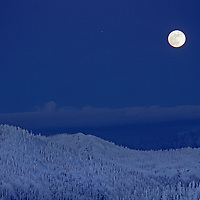 The  Moon rises over Glacier National Park, viewed from The Big Mountain ski area.