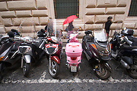 A pink scooter parked in Rome Italy, woman walking by with a red umbrella