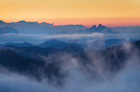 Fog rolling over summits of the North Cascades at sunset
