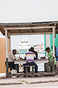 Men play cards at a roadside food stall at Potter's Cay in Nassau, Bahamas.
