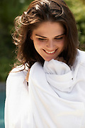 Close up portrait of happy woman outdoor wrapped up in white robe
