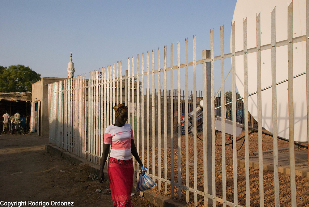 A woman passes by a satellite dish repeating the signal of the mobile phone network in the town of Abyei.