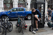 After locking his bike to a secure bar, a cyclist changes footwear next to a phone box in the City of London, the capitals financial district, on 25th April 2019, in the City of London, England.