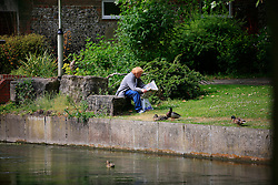 UNITED KINGDOM HAMPSHIRE 17JUN09 - Homeless man reads a newspaper near the chalkstream river Itchen in Winchester in Hampshire, southern England...The river has a total length of 28 miles, and is noted as one of England's - if not one of the World's - premier chalk streams. It is designated as a Site of Special Scientific Interest and is noted for its high quality habitats, supporting a range of protected species...jre/Photo by Jiri Rezac / WWF UK..© Jiri Rezac 2009