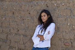 sexy woman leaning against an adobe wall in New Mexico