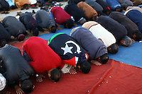 A rebel supporter wrapped in the red, black and green flag of the pre-Ghaddafi era's King Idriss, kneel in prayer in central Benghazi's Courthouse Square