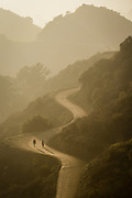 A couple make thier way down a trail in Griffith Park with the sun setting behind them.