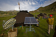 A Tibetan nomad walks outside one of the handmade yak wool tents that serves as a home to nomads during spring and summer in the Tibetan Plateau. The satellite dish and solar panel were provided by China's central government; along with a solar battery charger, a truck battery, and a TV so the nomads can watch Chinese broadcasts and learn the Chinese language; an attempt, some say, to assimilate indigenous Tibetans.