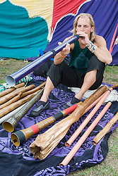 Young man blowing into a didgeridoo at the WOMAD (World of Music; Arts and Dance) Festival in reading; 2005,