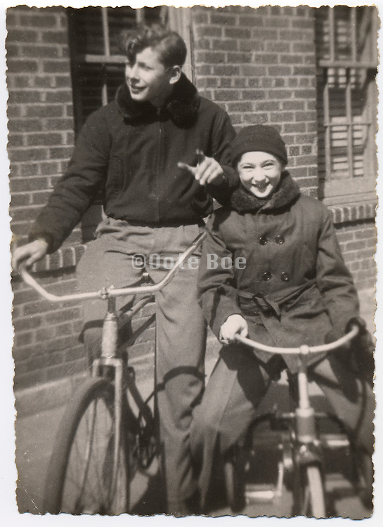 Two boys on there bicycle having fun