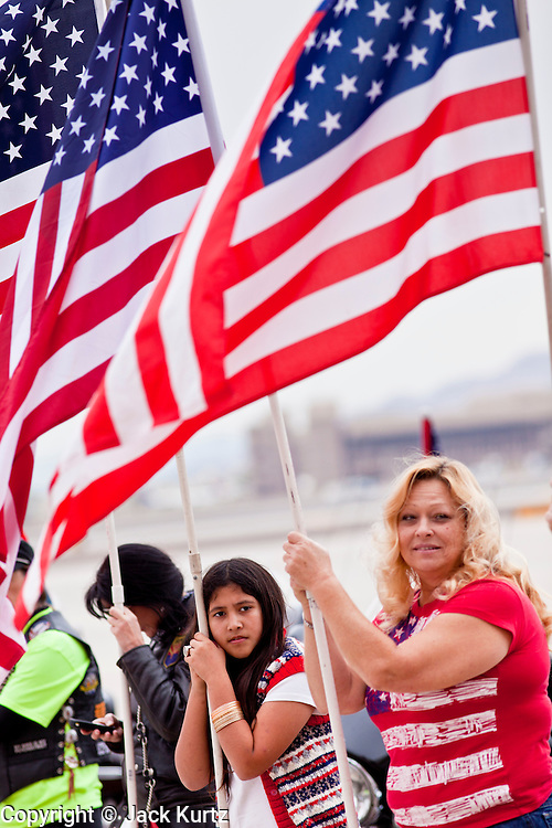 """15 JANUARY 2012 - PHOENIX, AZ:   Members of the Patriot Guard Riders form an honor guard for returning solders at the The 161st Air Refueling Wing of the Arizona Air National Guard in Phoenix. About 100 soldiers of A (Alpha) Company of the 422nd Expeditionary Signal Battalion (referred to as """"Alpha 4-2-2"""") of the Arizona Army National Guard returned to Arizona on Sunday, Jan. 15, following a nearly year-long deployment to Afghanistan. More than 10,000 Arizona Army and Air National Guard Soldiers and Airmen have been ordered to federal active duty in support of Operations Noble Eagle, Enduring Freedom, Iraqi Freedom, and New Dawn since September 2001. Approximately 200 Arizona National Guard Soldiers and Airmen are still serving on federal active duty overseas.   PHOTO BY JACK KURTZ"""