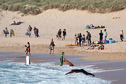 © Licensed to London News Pictures. 20/05/2020. Padstow, UK. Members of the public enjoy the warm weather on Constantine Bay on the north coast of Cornwall during a spell of hot weather. The weather in the south-west is forecast to be warm for the following week. Photo credit : Tom Nicholson/LNP