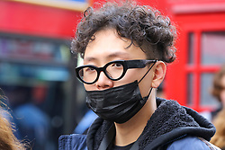 © Licensed to London News Pictures. 14/02/2020. London, UK. A fashion enthusiast wearing a surgical face mask arrives to the London Fashion Week shows in The Strand. The latest Coronavirus patient in London is linked to 'super spreader' attended transport conference with 250 people in Westminster. Photo credit: Dinendra Haria/LNP