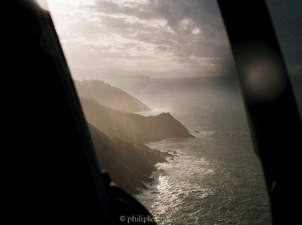 Seen from a hilltop at dusk, waves crash onto cliffs near the city of San Sebastian in Spain