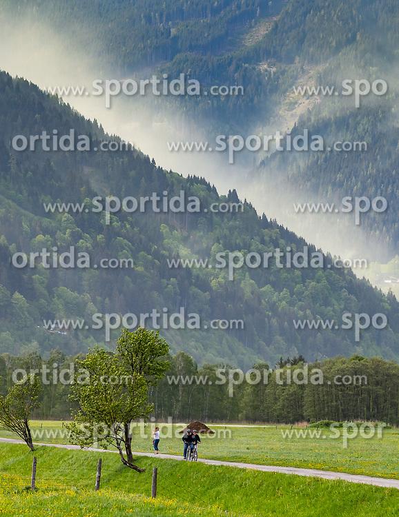 THEMENBILD - Fahrradfahrer auf einem Weg, dahinter eine vom Wind aufgewirbelte Pollenwolke über der Schmitten, aufgenommen am 29. April 2018 in Zell am See, Österreich // Cyclists on a road, behind them a cloud of pollen swirled by the wind hangs over the the Schmitten in Zell am See, Austria on 2018/04/29. EXPA Pictures © 2018, PhotoCredit: EXPA/ JFK