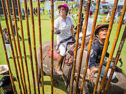 "28 AUGUST 2014 - BANGKOK, THAILAND:     A mahout and polo player selects a polo mallet for the player at the King's Cup Elephant Polo Tournament at VR Sports Club in Samut Prakan on the outskirts of Bangkok, Thailand. The tournament's primary sponsor in Anantara Resorts. This is the 13th year for the King's Cup Elephant Polo Tournament. The sport of elephant polo started in Nepal in 1982. Proceeds from the King's Cup tournament goes to help rehabilitate elephants rescued from abuse. Each team has three players and three elephants. Matches take place on a pitch (field) 80 meters by 48 meters using standard polo balls. The game is divided into two 7 minute ""chukkas"" or halves.  PHOTO BY JACK KURTZ"