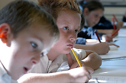 Schoolboys writing in lesson in classroom; primary school; West Yorkshire; UK