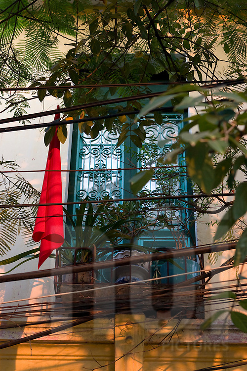 View of a window  with metallic decorative motives. A red flag hung on the side. Hanoi, Vietnam, Asia.