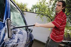 Young Czech man washing car,