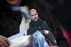 A Manchester City fan carries a cardboard cutout of Manchester City manager Pep Guardiola ahead of the match
