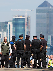 © Licensed to London News Pictures. 05/05/2016. Police officers stop to admire the view across to Canary Wharf from sunny Greenwich Park. Credit : Rob Powell/LNP