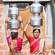 INDIVIDUAL(S) PHOTOGRAPHED: Shehla Vithal Parate (right). LOCATION: Ahirwade, Maharashtra, India. CAPTION: Shehla (right) and her neighbour collect water before carrying it back to their homes. Prasad, who lives next door to them, recently had a biogas unit installed by Sistema Biobolsa.