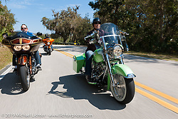 Laura Klock riding a green custom Harley-Davidson dresser through Tomoka State Park with her husband Brian following just behind her during Daytona Bike Week. FL, USA. March 11, 2014.  Photography ©2014 Michael Lichter.