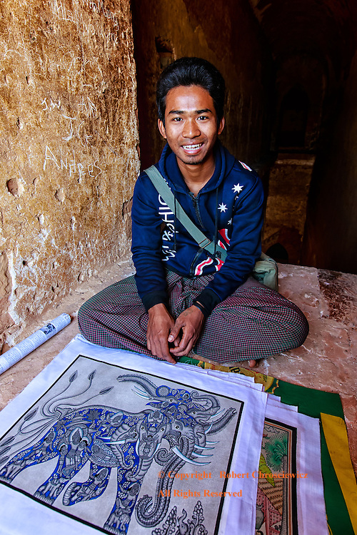 A Kind Salesman: A kind, smiling young artist, with his paintings at his feet, attempts a sale in the ruins of a Buddhist temple, Bagan Myanmar.
