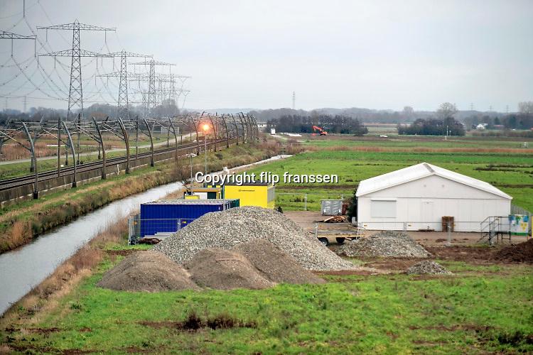 Nederland, Bemmel, 22-12-2020 Vanaf knooppunt Ressen wordt de a15, een voor de regio Arnhem en Nijmegen belangrijke schakel in de verbinding naar Duitsland, doorgetrokken naar de A12 tussen Duiven en Zevenaar. Na jaren discussie en uitstel, moet het 1 miljard kostende traject aangelegd worden, niet met de gewenste tunnel bij Groessen, maar een brug over het Pannerdensch Kanaal . Tegen met name de brug is bezwaar gemaakt door omwonenden vanwege aantasting van het natuurgebied de rijnstrangen en geluidsoverlast. De raad van state zal hier na lang uitstel binnenkort uitspraak over doen. De weg zal grotendeels parallel aan de betuwelijn lopen. Op verschillende plekken vinden voorbereidende werkzaamheden plaats.Foto: ANP/ Hollandse Hoogte/ Flip Franssen
