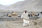 """An Afghan villager tends a field outside a """"Qalat"""" used by US mentors living with Afghan National Army soldiers rented from a nearby village in Tagab Valley.  In the background is the graded road being paved to help the valley.....It is part of the counterinsurgency effort to connect with villagers, gather intelligence and provide local security.....Colonel Haynes said fixating solely on the enemy is a mistake.  His men are on the sharp end of the fight taking calculated risks as COIN doctrine prescribes.  The Marines' COIN strategies come from lessons learned by the French and British as well as their own history.  During the Vietnam War the Marines employed a similar COIN idea with some success known as """"Combined Action Programs (CAP's).""""  They lived in villages and fought alongside indigenous Vietnamese security forces.  Marine General Victor """"Brute"""" Krulak defended the program and waged his own internal policy war with Army General Westmoreland.  Krulak lost his battle with Westmoreland who preferred massive firepower and body counts - a strategy that wreaked havoc on the civilian population.  .."""