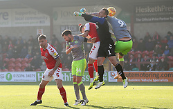 Fleetwood Town's Alex Cairns punches clear under pressure from Walsall's Andy Cook