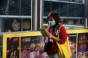 A woman with a yellow bag wears a green face mask. She walks and reads her iPad at the same time. 7 million people live on 1,104km square, making it Hong Kong the most vertical city in the world.
