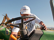 31 JULY 2009 --  BUCKEYE, AZ: Erasmo Flores, 12, from Laredo, TX, starts a tractor to check the hours on it at the auction on the former Pylman Dairy Farm in Buckeye. The auction was handled by Overland Stockyards from Hanford, CA. The Arizona dairy industry is struggling to survive the worst milk economy some have ever seen. Due to the global recession, overseas demand for Arizona dairy products has plummeted, forcing prices down while production costs have stayed stable or gone up. For every $1 dairymen earn from milk sales, it cost them $1.50 to produce the milk. Photo by Jack Kurtz