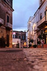 Vicolo del centro di Ostuni col manto stradale in basolato al tramonto. sullo sfondo uno scorcio della piazza municipio