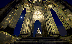 Edinburgh at Night - The moon appears between the columns of the Scott Monument on Edinburgh's Princes Street and appears to light up the statue of Sir Walter Scott