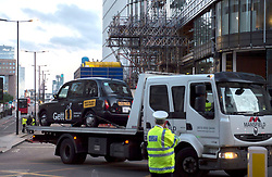 A cab is removed from a police cordon on London Bridge following last night's terrorist incident.