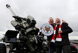 Fans with a military weapon outside the ground before the match