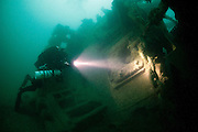 A technical diver explores the wrecked bow of the Liberty Ship Fort Yale, which lies on its side. Sunk by torpedo in 1944, English Channel, United Kingdom