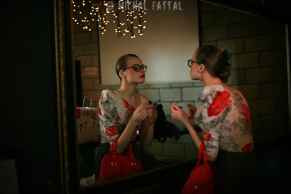 An Israeli model checks herself in front of the mirror behind the scenes of a fashion show marking the International Women's Day in Tel Aviv.