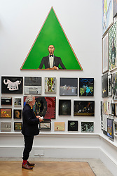 "© Licensed to London News Pictures. 08/06/2017. London, UK. A visitor views artworks on display, overlooked by ""Mr Green Looking At His Wife"" by Anthony Green RA.  Preview of the Summer Exhibition 2017 at the Royal Academy of Arts in Piccadilly.  Co-ordinated by Royal Academician Eileen Cooper, the 249th Summer Exhibition is the world's largest open submission exhibition with around 1,100 works on display by high profile and up and coming artists.<br />  Photo credit : Stephen Chung/LNP"